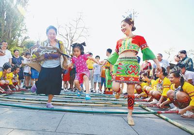 2月6日,在海南三亚南山景区的新春庙会上,游客和黎族阿妹一起跳竹竿舞