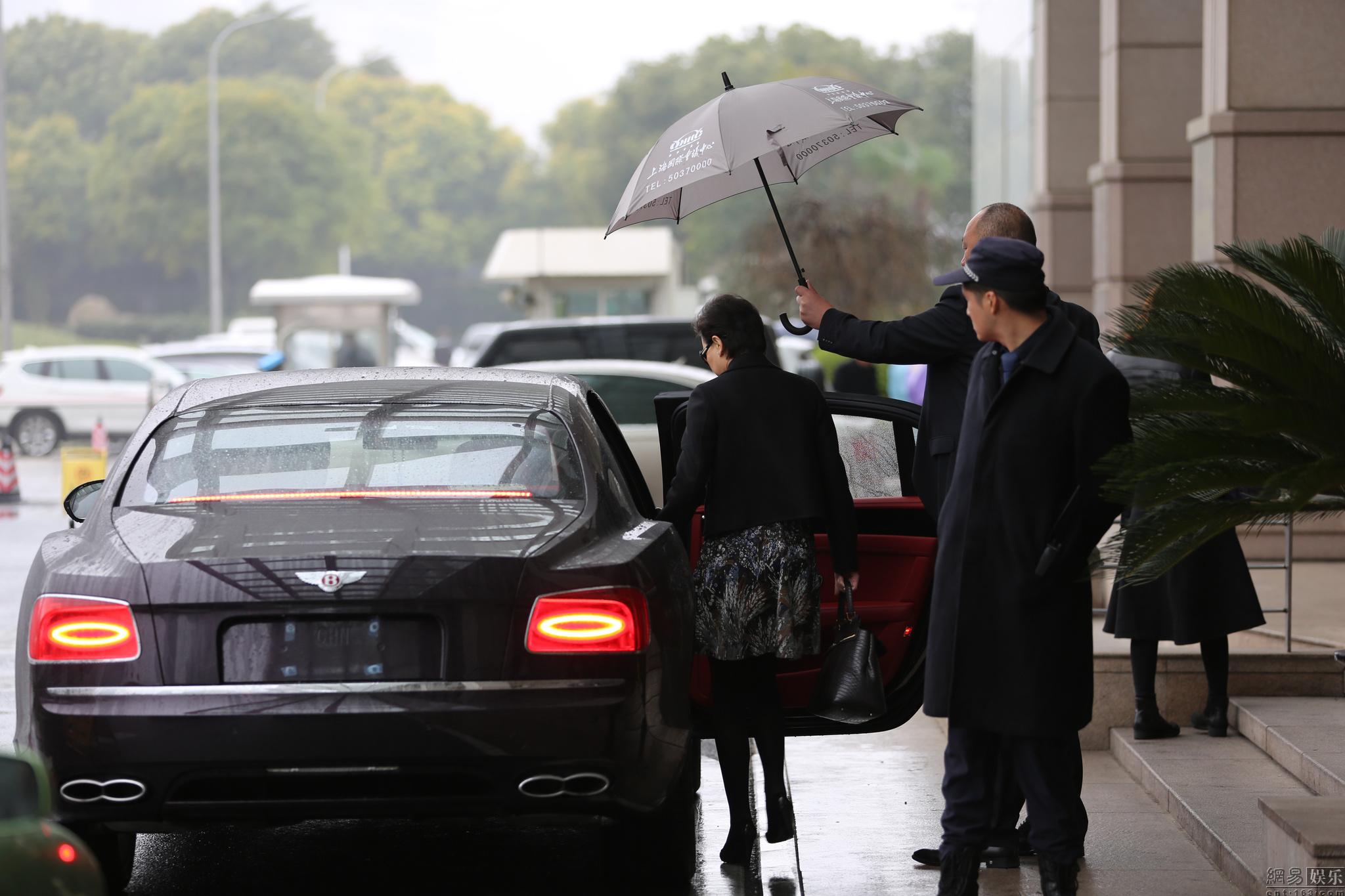 杨澜获高大保镖撑伞避雨上宾利车